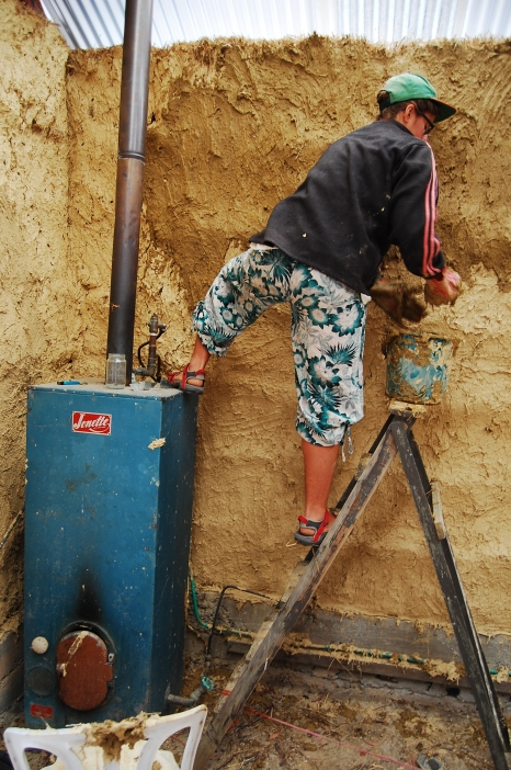 Smearing mud on the straw-bale house, volunteering in Australia