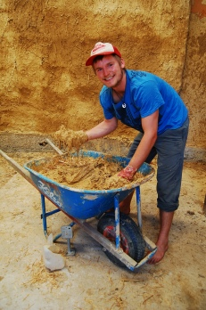 James mixing clay, sand, water and hay